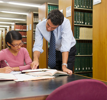Businessman and woman doing research in library