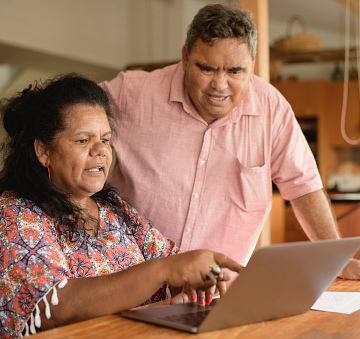 Aboriginal couple at home using the internet on a laptop, man leaning over woman and looking at screen