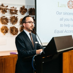 MinterEllison Partner Lee Rossetto standing at the lecturn and opening the Law Access Thank You Drinks event